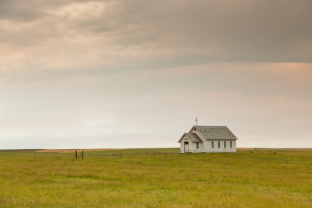 A small old white wooden church wtih a cross on top sits on an open prairie with a thunder cloud rolling in. Stock Photo