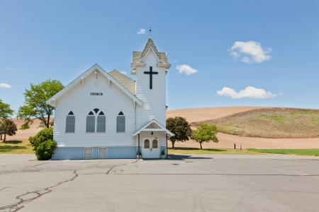 A small white church with a black cross, a cracked parking lot, and small trees sits on the prairie of Eastern Washington.