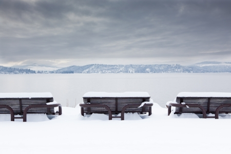 Three metal benches by  lake Coeur dAlene, Idaho are covered in snow with mountains and storm clouds in the background.