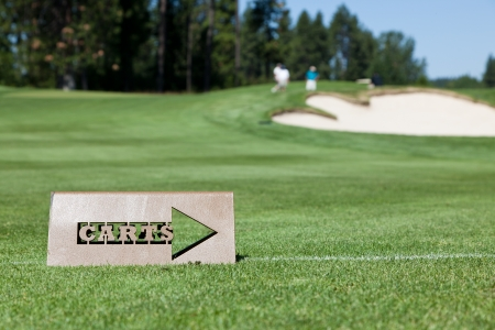 A cut out metal sign tells golf carts when to head back to the path off the green. Background of golfers by the sand trap and hole. photo