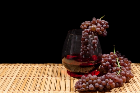 Red wine grapes next to and inside of a wine glass with red wine on a bamboo surface and isolated against black. Stock Photo