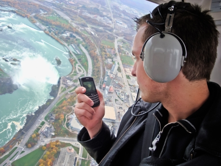 A young man in a helicopter uses his cell phone camera to take a photo of Niagara Falls