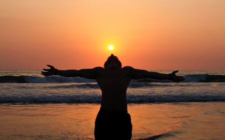 shadow: A young man stands as a living shadow  in front of the ocean with his arms outstreatched to the orange sky and his head tilted back to absorb the setting sun  Stock Photo