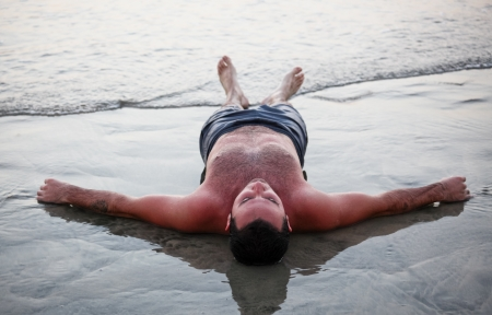 A young man lays exhausted on the beach after a long day of sun and fun in the water  photo