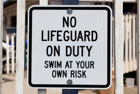 warns: A black and white sign nailed to a wooden railing warns of no lifeguard on duty. Stock Photo