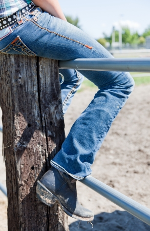 jeans boots: The leg of a young woman in blue jeans and dirty cowboy boots sitting on a fence.