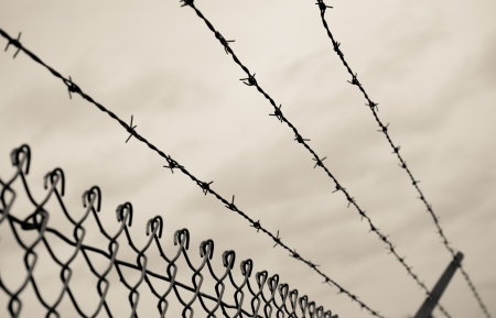 Three rows of barbed wire on top of a chain link fence with an aged photo look. Stock Photo