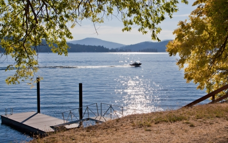 A small boat passing through a strip of sun sparkles on a blue lake framed by shoreline with a dock and fall tree branches. photo