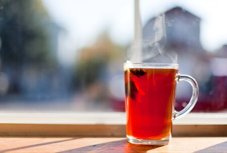 A clear glass cup of hot tea with a floating tea bag and a anise star with steam rising. blurred domestic background. photo