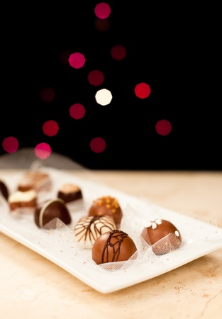 Hand made chocolates with gold glitter netting on a white plate with a marble counter top. Isolated black background with blurred lights.