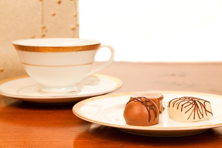 Three artisan chocolates on a gold rimed china plate with a matching tea cup and saucer. isolated white background. 版權商用圖片