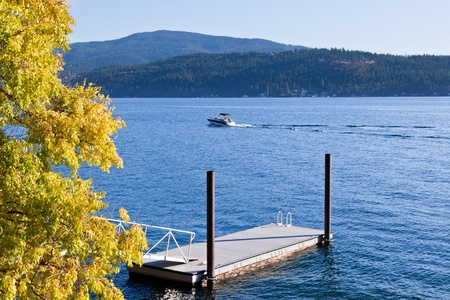 A small boat on a blue lake during early fall with changing trees by a floating dock and mountains in the distance.