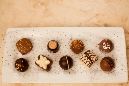 guilty pleasures: Hand made artisan chocolates nestled in gold glitter netting on a white plate with a marble counter top background. Stock Photo