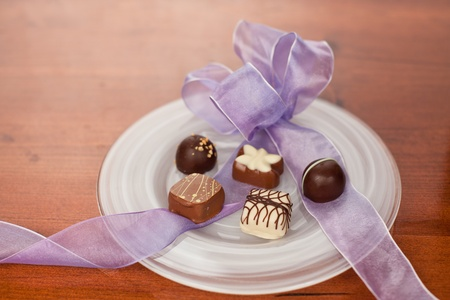 guilty pleasures: Hand made artisan chocolates on a white plate with a purple ribbon bow and a wooden counter background.