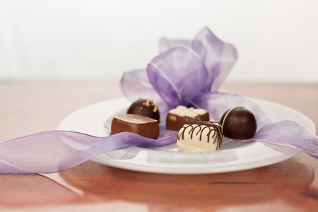 guilty pleasures: Hand made artisan chocolates on a white plate with a purple ribbon bow and a wooden counter background