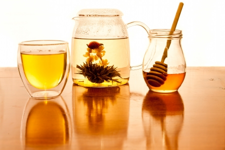 A hand made green tea flower pod floats in a glass teapot with a double walled tea cup and honey jar with drizzle stick