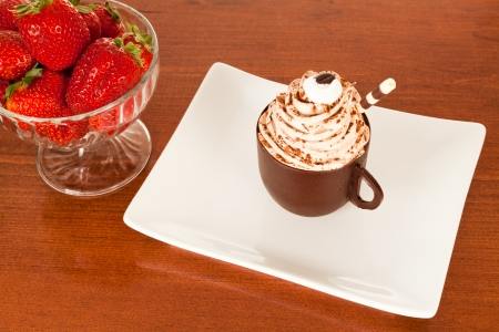 A chocolate cup full of coffee mousse on a white plate with a glass bowl of strawberries on a wooden table  photo