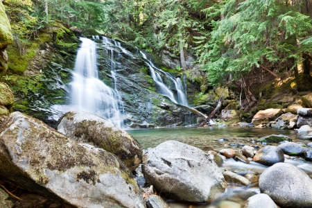 Upper Snow Creek Falls in late summer with silky water flowing over moss covered rock, large boulders in the creek bed, and framed by evergreen trees. photo