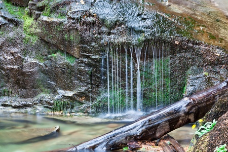 Water drips off of a moss covered rock at the base of a waterfall to create a curtain of silky water flowing into a creek. Stock Photo - 16156551