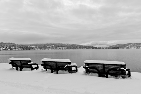 Three black metal benches overlooking the lake and mountains are covered in snow in a black and white winter scene. photo