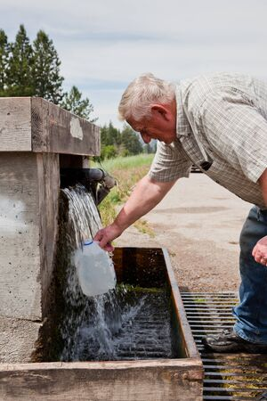 A silver haired man is bending over filling up a plastic water jug from a underground spring that is pumped to the surface. photo