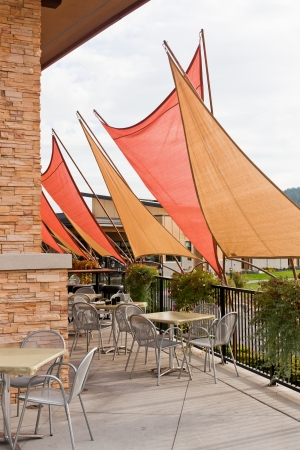 Gold and orange triangle awnings create a shaded area for diners at outdoor patio chairs and tables. Stock Photo