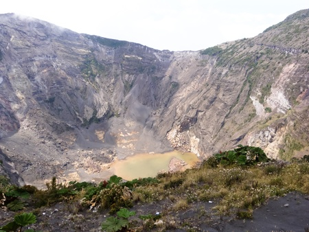 pooled: Looking over the rim and into the crater of Irazu volcano with dark volcanic soil, sulfur pooled water, and an isolated sky background.