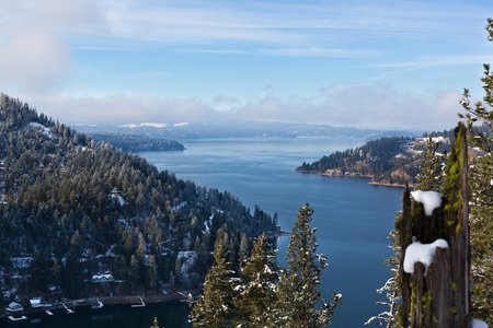 Morning fog lifting above the blue water of Lake Coeur d Alene in winter with snow covered trees. photo