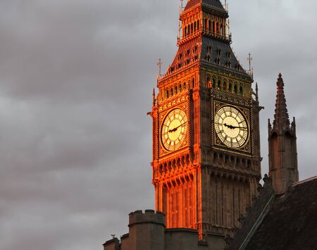 Double clock faces of Big Ben Tower with the Western clock face glowing brilliant orange from the setting sun. photo