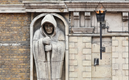 A statue of a cloaked and hooded monk like figure is built into a wall of a building with an ever burning gas torch in London, England. Stock Photo - 17448385