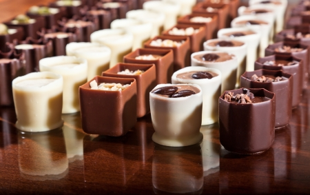 Rows of dark, milk, and white chocolate truffle cups displayed on a shiny wooden surface. photo