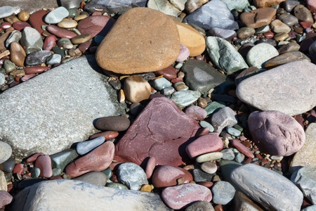 River rocks in a variety of colors that have been worn smooth by tumbling downstream on a riverbank in the sunshine. Background. Stock Photo - 18027353