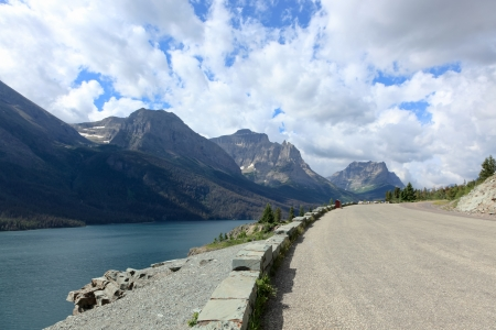 A curved road beside a green lake leads into a scene of dramatic mountains and sky in Glacier National Park, Montana. Stock Photo - 18307433