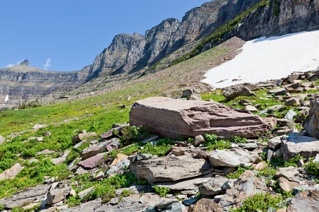 A large red boulder lays among a debris field of smaller rocks which have all fallen from the high cliffs of the mountains above. Glacier National Park, Montana. Stock Photo - 18308232
