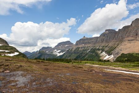 soggy: mountains trail off in the distance with a green valley and a soggy creek from melting snow in Glacier National Park, Montana. Stock Photo