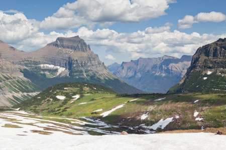 high plateau: A high plateau in summer with snow melting into green fields surrounded by enormous mountains of Glacier National Park, Montana.