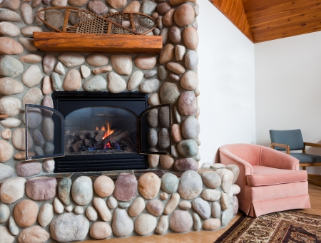 A gas fireplace set in  colorful river rocks with a wooden mantle topped with vintage snowshoes in a white living room with chairs and a rug. photo
