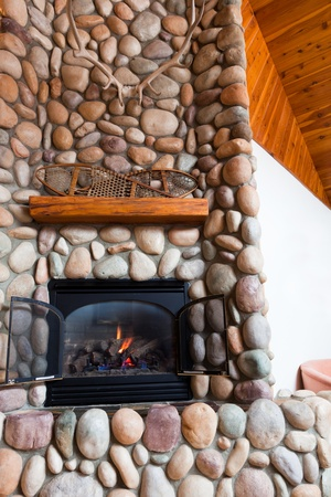 A gas fireplace set in  colorful river rocks with a wooden mantle topped with vintage snowshoes and large deer horns in a cabin in Idaho.