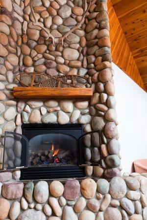 chemin�e gaz: Un foyer � gaz situ� dans la rivi�re des roches color�es avec un manteau en bois garnie de raquettes vintage et de grandes cornes de cerf dans une cabane en Idaho.