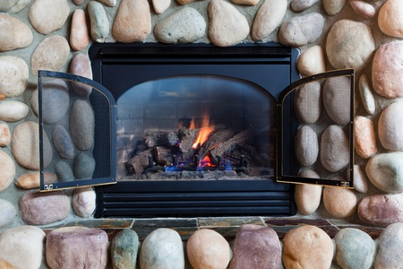 A black metal framed gas fireplace set in  colorful river rocks with blue and orange flames in a cabin in Idaho. photo