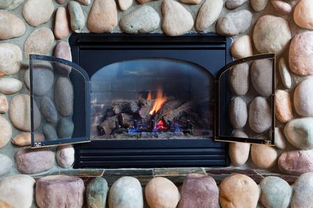chemin�e gaz: Une chemin�e en m�tal noir encadr� de gaz mis en roches de rivi�re color�s avec des flammes bleues et oranges dans une cabane en Idaho.
