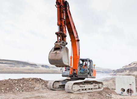 operates: Un operaio edile maschio gestisce una traccia macchina-zappa su un luogo di lavoro riva del fiume in una giornata nuvolosa.
