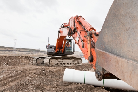A male heavy equipment operator sits in an orange track-hoe machine with the arm extended out in front resting on the dirt.