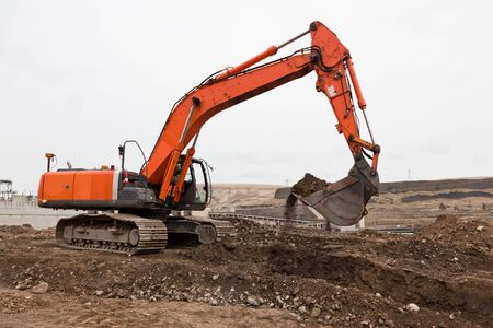 An orange track-hoe is moving dirt and rock out of a ditch with loose dirt spilling out of the bucket with a cloudy sky background. Imagens