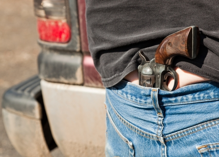 waistband: A well worn revolver with a wooden grip is tucked into a mans jeans hidden at the small of his back.