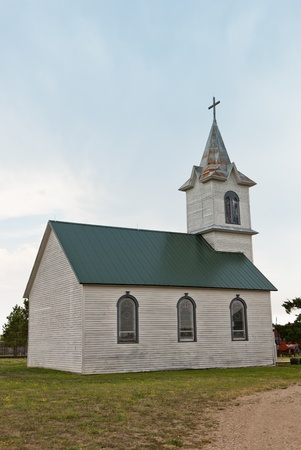 An old prairie church with faded paint and a rusty steeple in South Dakota