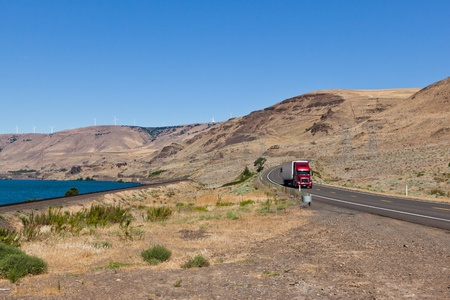 A two lane road with a red semi truck driving through the Columbia River Gorge on the Washington State side on a sunny summer day. photo