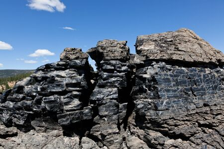 large formation: A large formation of black obsidian lava flow cracked by weather and erosion in Newberry National Volcanic Monument, Oregon. Stock Photo