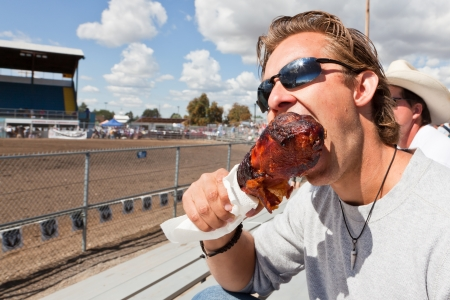 A young man taking a big bite of a deep fried turkey leg as a snack at a rodeo in Northern Idaho.