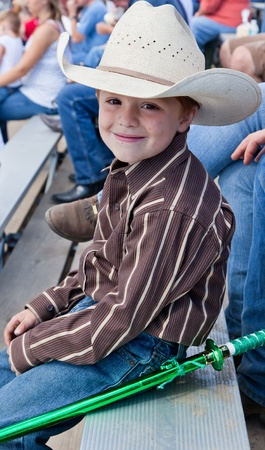 A young cowboy sitting on bleachers watching a rodeo with a plastic ninja sword tied to his jeans. Archivio Fotografico
